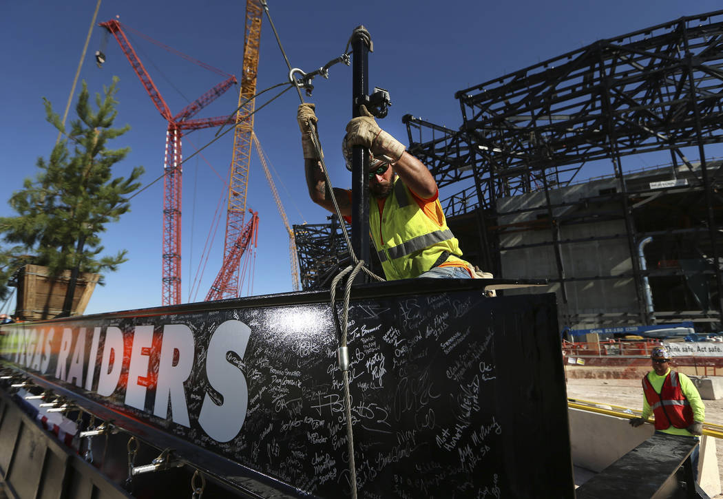 Zac Carter, iron worker with Local 597, secures a steel beam during the Las Vegas Stadium Toppi ...