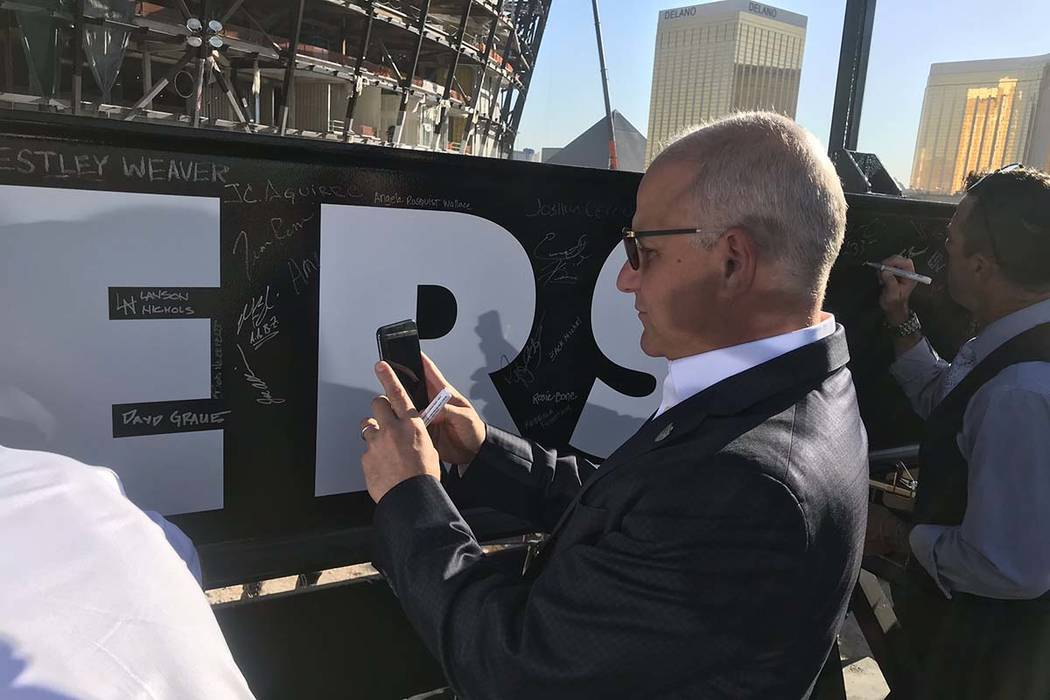 Raiders President Mark Badain takes a picture of his signature after he signed a beam that will ...