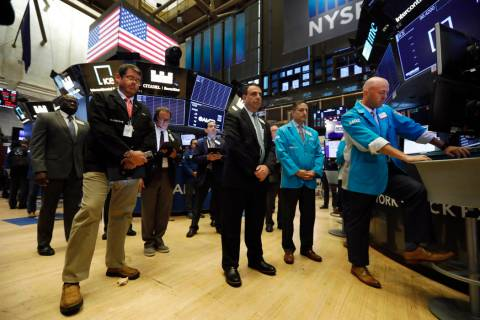 Traders pause for a moment of silence on the floor of the New York Stock Exchange, for the vict ...