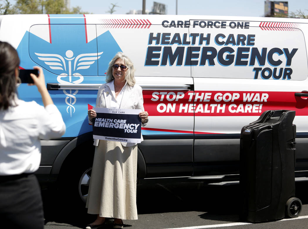 U.S. Rep. Dina Titus, D-Nev., takes a photo in front of the Protect Our Care's nationwide bus ...