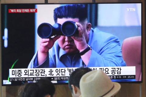 FILE - In this Aug. 2, 2019, file photo, people stand by a TV screen showing a file footage of ...