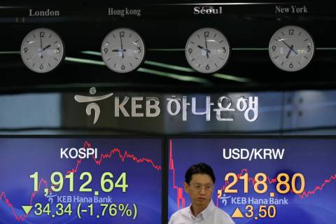 A currency trader walks by the screens showing the Korea Composite Stock Price Index (KOSPI), l ...