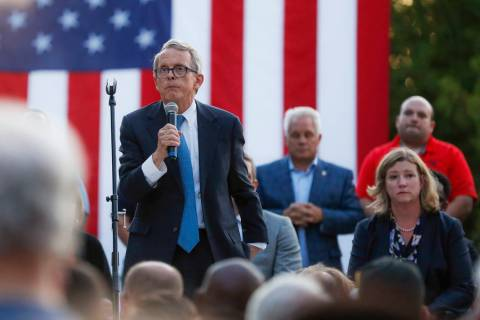 Ohio Gov. Mike DeWine, left, speaks alongside Dayton Mayor Nan Whaley, right, during a vigil at ...