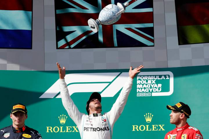Mercedes driver Lewis Hamilton, center, of Britain, celebrates on the podium with second placed ...