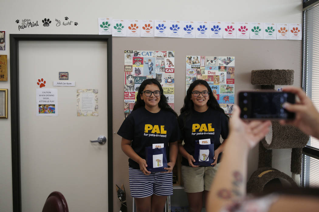 Anaisa, left, and Malena Maestas, 13, get their photo taken during the soft launch at the Rescu ...
