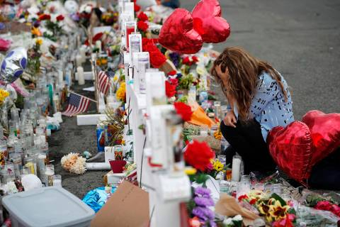 Gloria Garces kneels in front of crosses at a makeshift memorial near the scene of a mass shoot ...