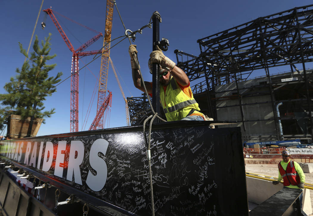 Zac Carter, iron worker with Local 597, secures a steel beam during the Allegiant Stadium Toppi ...
