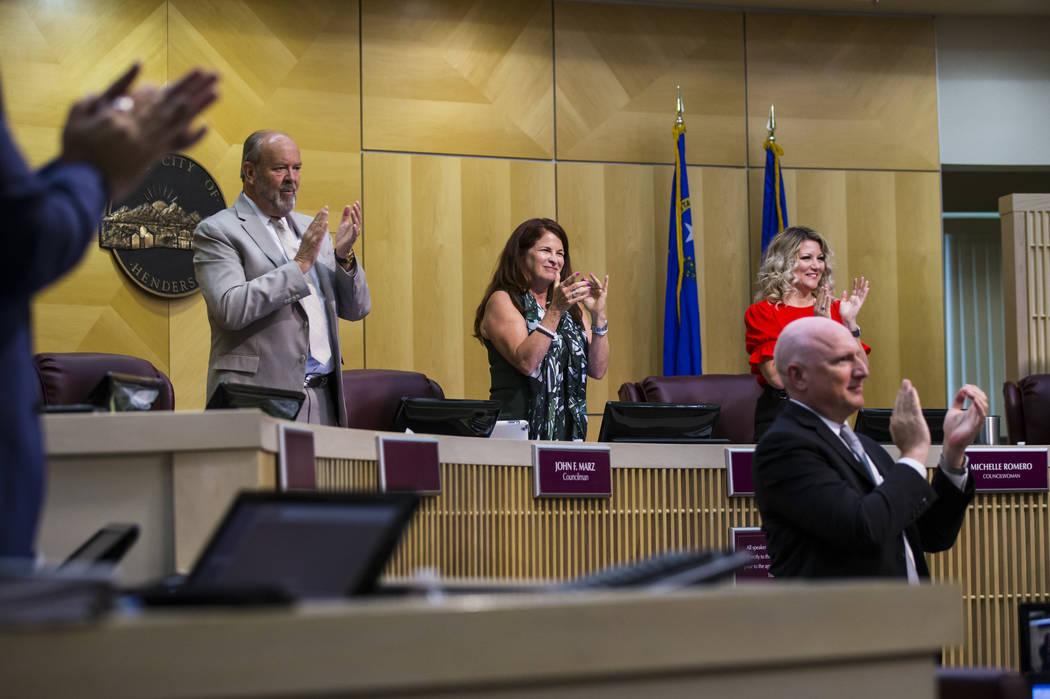 Henderson Mayor Debra March, center, claps alongside councilman John Marz, left, and councilwom ...
