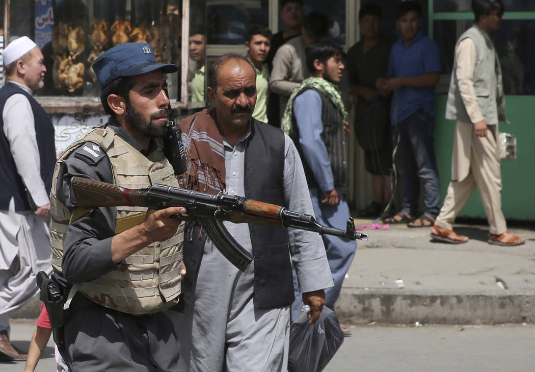 An Afghan policeman stands guard after an explosion near the police headquarters in Kabul, Afgh ...