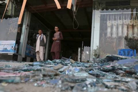 Afghans stand near a damaged shop after an explosion in Kabul, Afghanistan, Wednesday, Aug. 7, ...