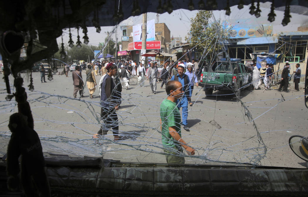 Afghans are seen through a shattered glass of a transport bus broken after an explosion in Kabu ...