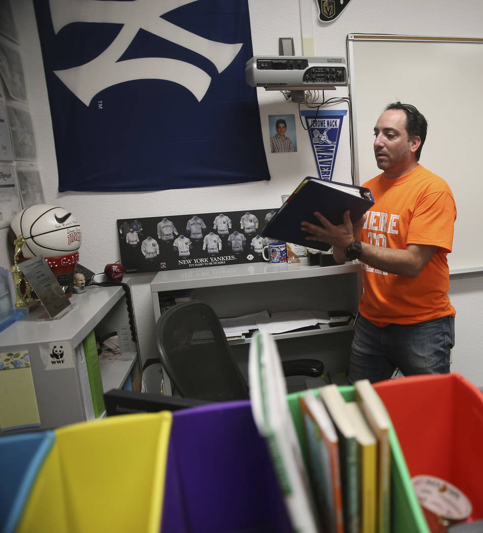 English teacher Lloyd Goldberg pulls out a binder filled with school material applications for ...