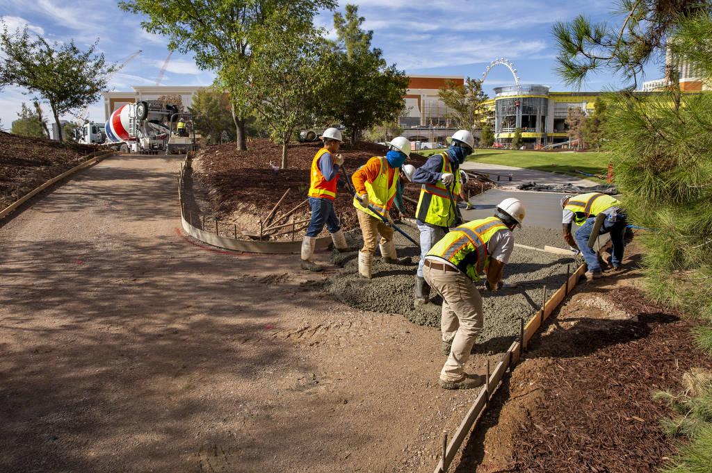 Construction crew lay a concrete path at Wynn Golf Club on Tuesday, July 30, 2019, in Las Vegas ...
