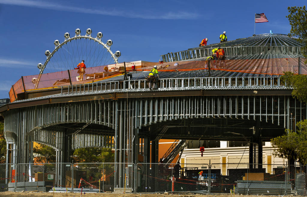 A construction crew works on the roof of a new pavilion at Wynn Golf Club on Tuesday, July 30, ...