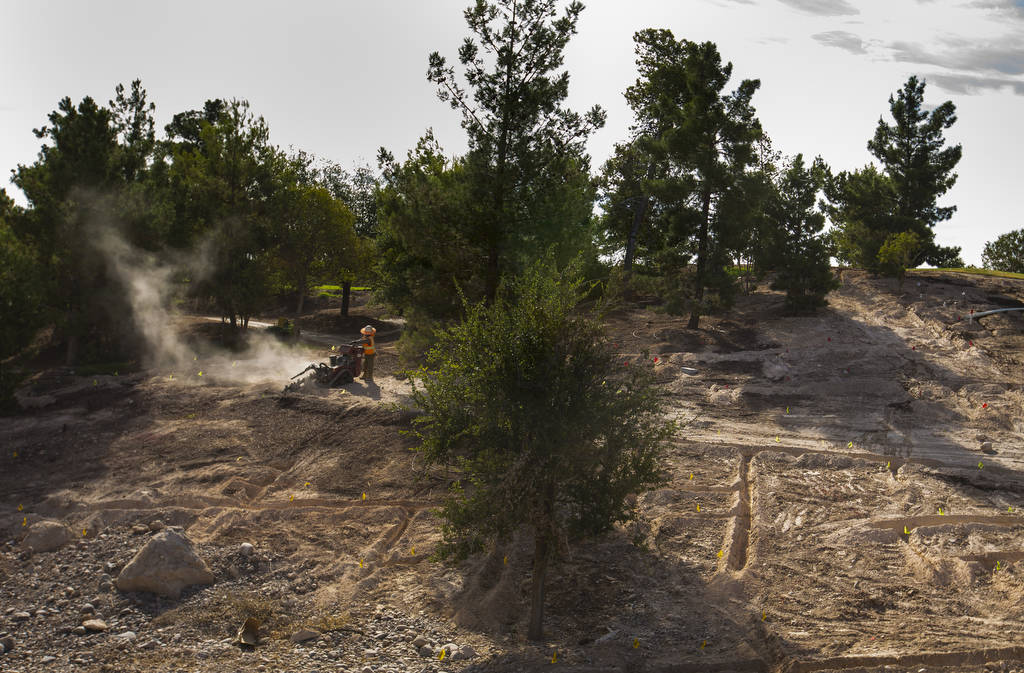 A construction worker carves a concrete path out of the landscape at Wynn Golf Club on Tuesday, ...