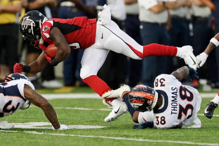 Denver Broncos' Shamarko Thomas (38) tackles Atlanta Falcons' Marcus Green (3) on a punt return ...