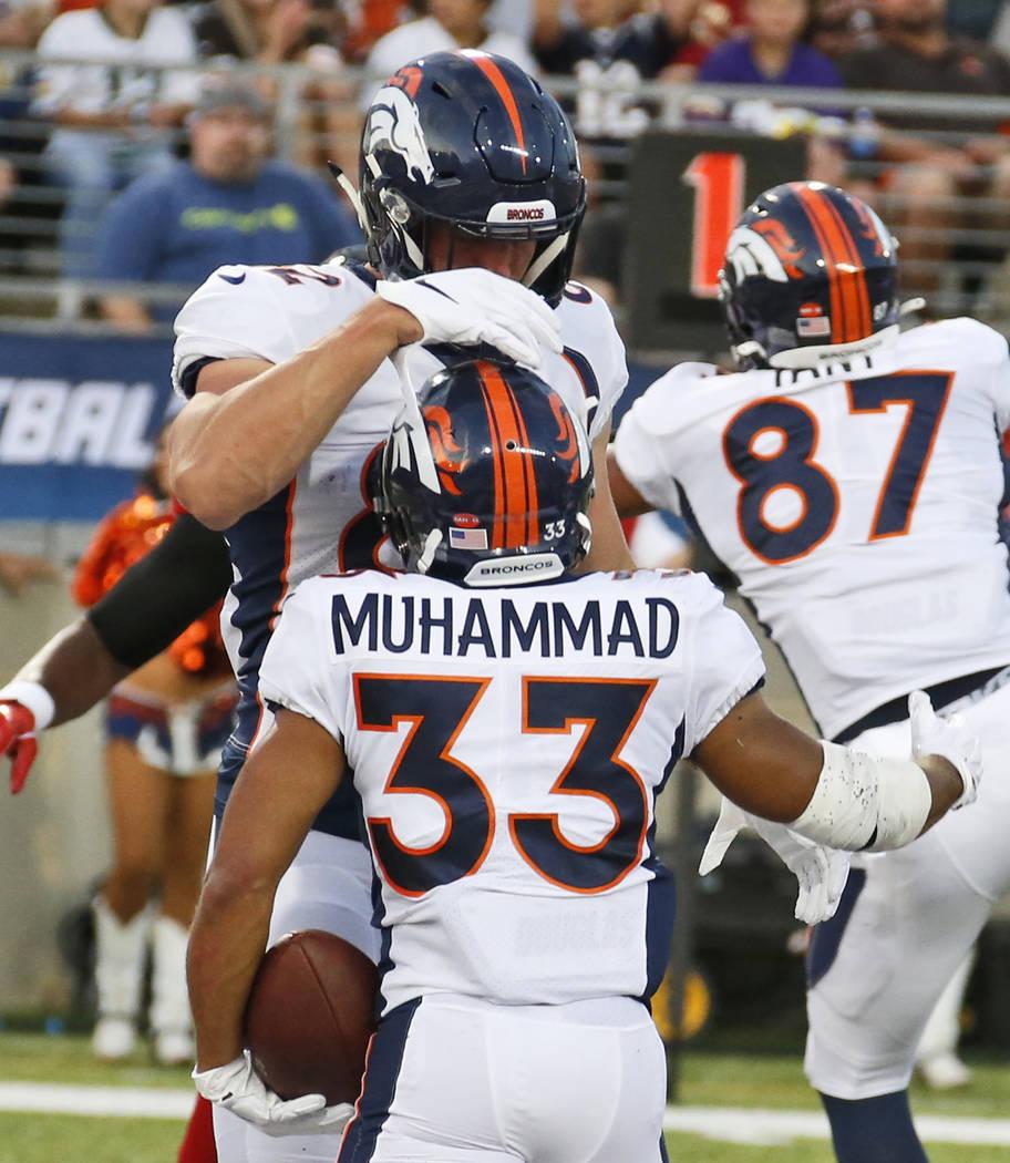 Denver Broncos fullback Andy Janovich, top, congratulates running back Khalfani Muhammad after ...