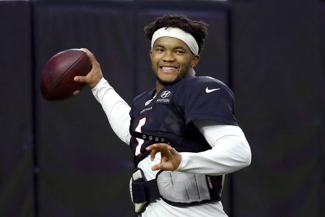 Arizona Cardinals quarterback Kyler Murray smiles as he throws a pass during an NFL football tr ...
