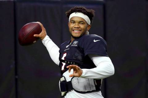 Arizona Cardinals quarterback Kyler Murray smiles as he throws a pass during an NFL football tr ...