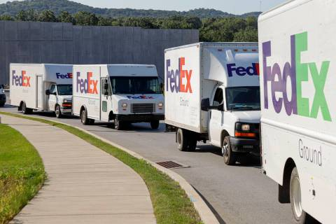 FILE - In this June 26, 2019, file photo delivery vehicles depart the FedEx Ship Center in Cran ...