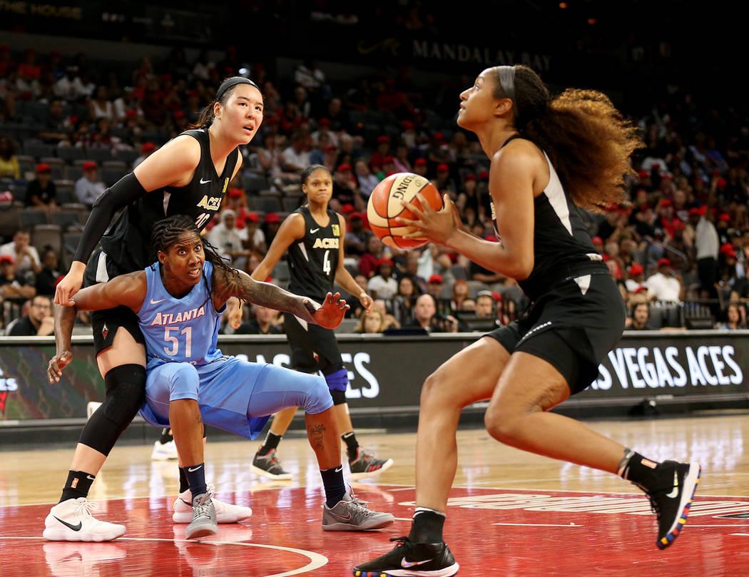 Las Vegas Aces' Jisu Park (19) is blocked by Atlanta Dream's (51) Jessica Breland as teammate J ...
