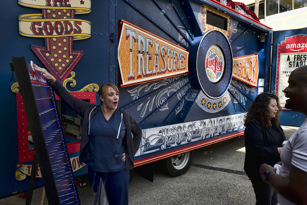 An office worker plays a carnival game for a free sample at an Amazon Treasure Truck at The Par ...