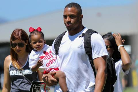 Oakland Raiders safety Johnathan Abram carries his daughter Harlee, 2, after a joint NFL traini ...