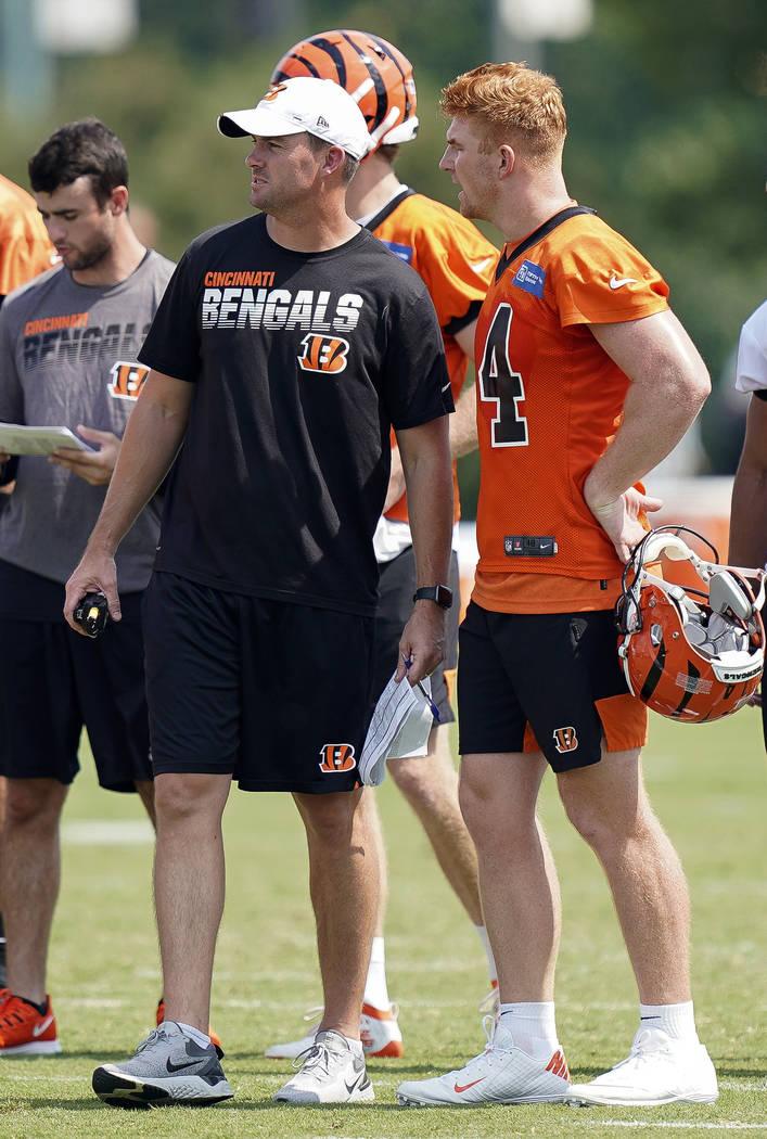 Cincinnati Bengals head coach Zac Taylor, front left, and quarterback Andy Dalton, right, talk ...