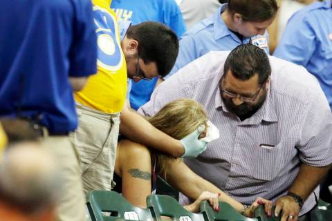 A fan is helped after being hit by a foul ball during the ninth inning of a baseball game betwe ...