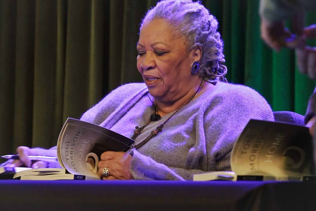 """In this Feb. 27, 2013 file photo, author Toni Morrison signs copies of her latest book """"Home."""" ..."""