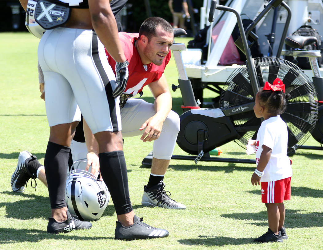 Oakland Raiders quarterback Derek Carr (4) talks to safety Johnathan Abram's two-year-old daug ...