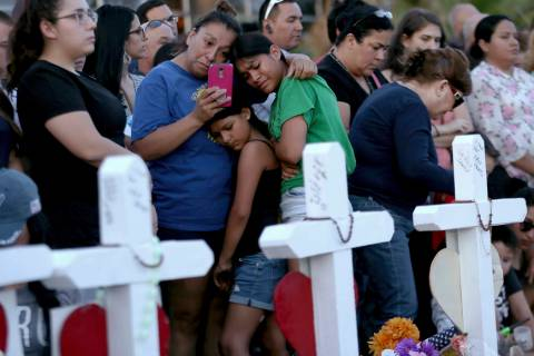 A mother clings to her daughters as they visit a memorial for the victims of Saturday's mass sh ...