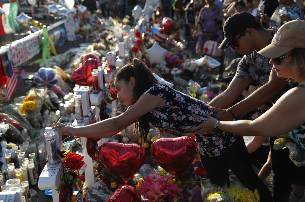 A woman leans over to write a message on a cross at a makeshift memorial at the scene of a mass ...