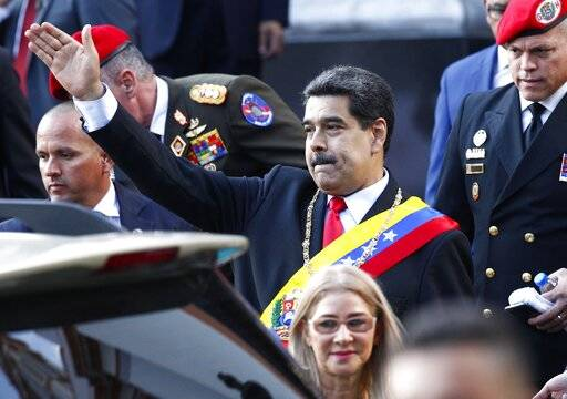 Venezuela's President Nicolas Maduro, accompanied by first lady Cilia Flores, waves to supporte ...