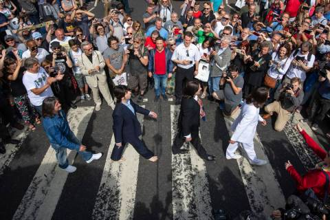 Thousands of fans gather to walk across the Abbey Road zebra crossing, on the 50th anniversary ...