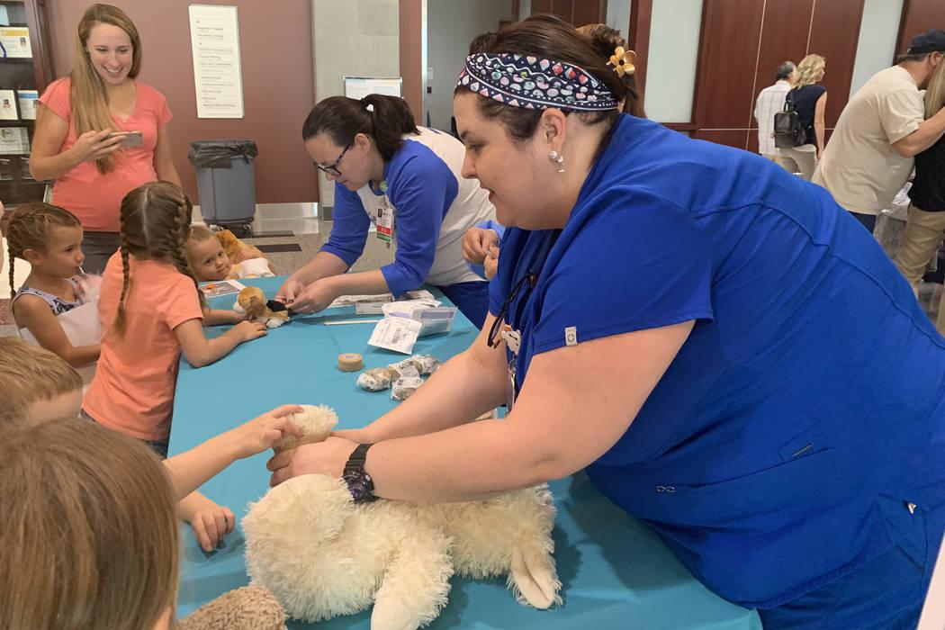 Demarri Vasquez, right, an emergency RN at Centennial Hills Hospital, wraps a cast around the l ...