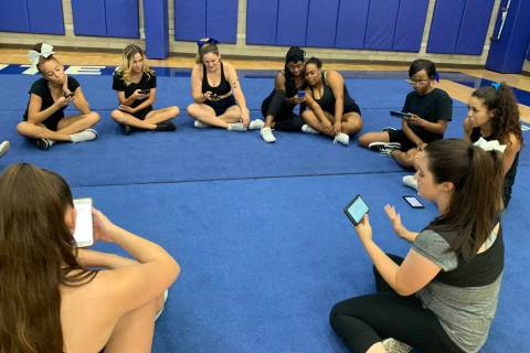 Tiffany Boulter, right, discusses dance routines with her cheer squad as they take a break from ...