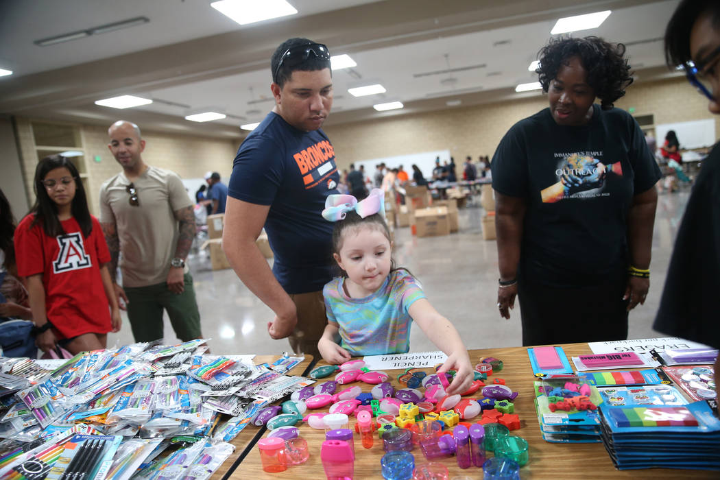 Volunteer LaShuna Proctor, right, assists Kyle Hammond and his daughter Lily, 5, with selecting ...