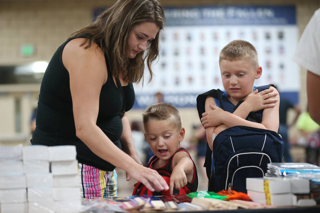 Kimberly Weller, from left, with her sons Owen, 6, and Brayden, 8, select free school supplies ...