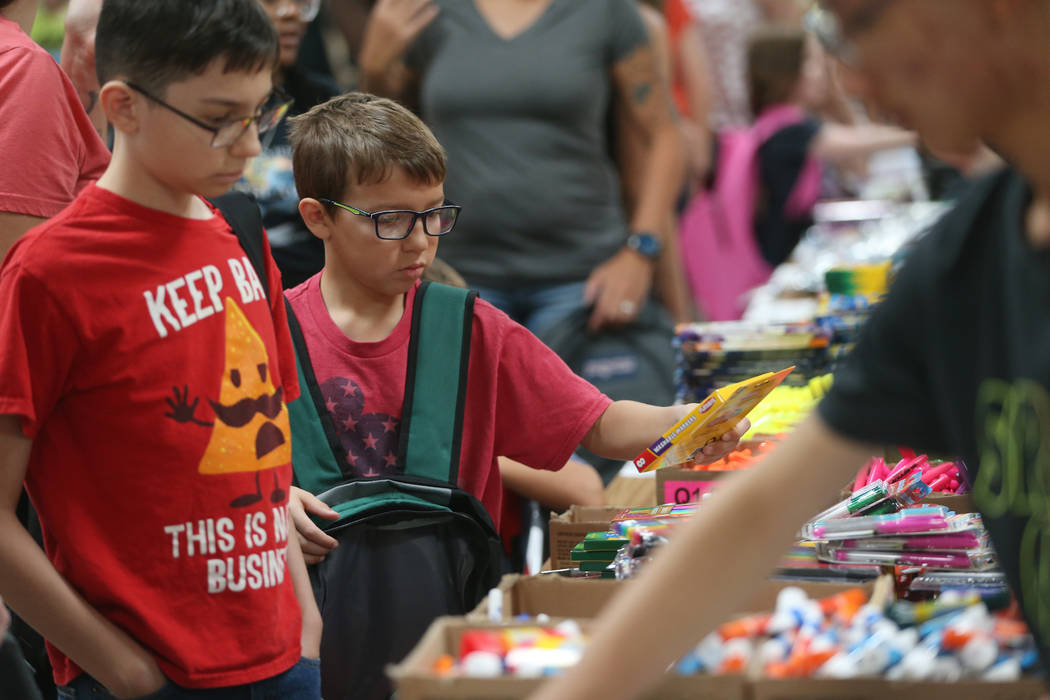 Lucas Stockmann, 13, left, and his brother Sebastian, 8, select free school supplies during an ...