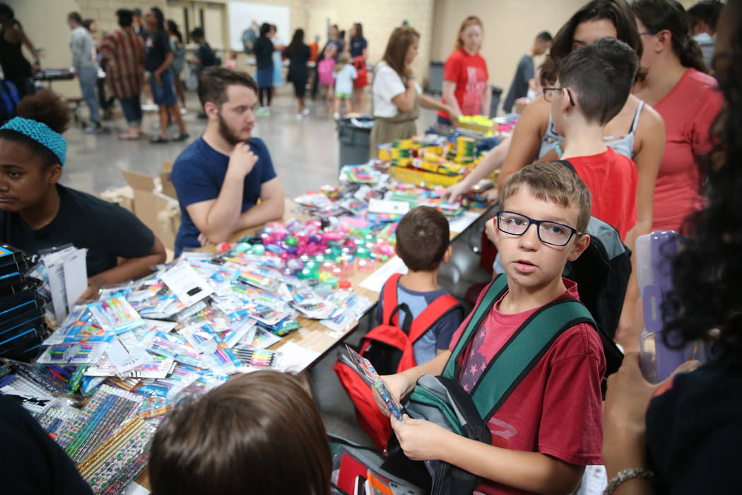 Eight-year-old Sebastian Stockmann, right, selects free school supplies during an event for mil ...