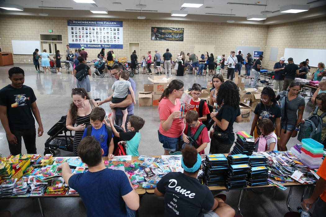 People attend an event for military families hosted by Operation Homefront where they received ...