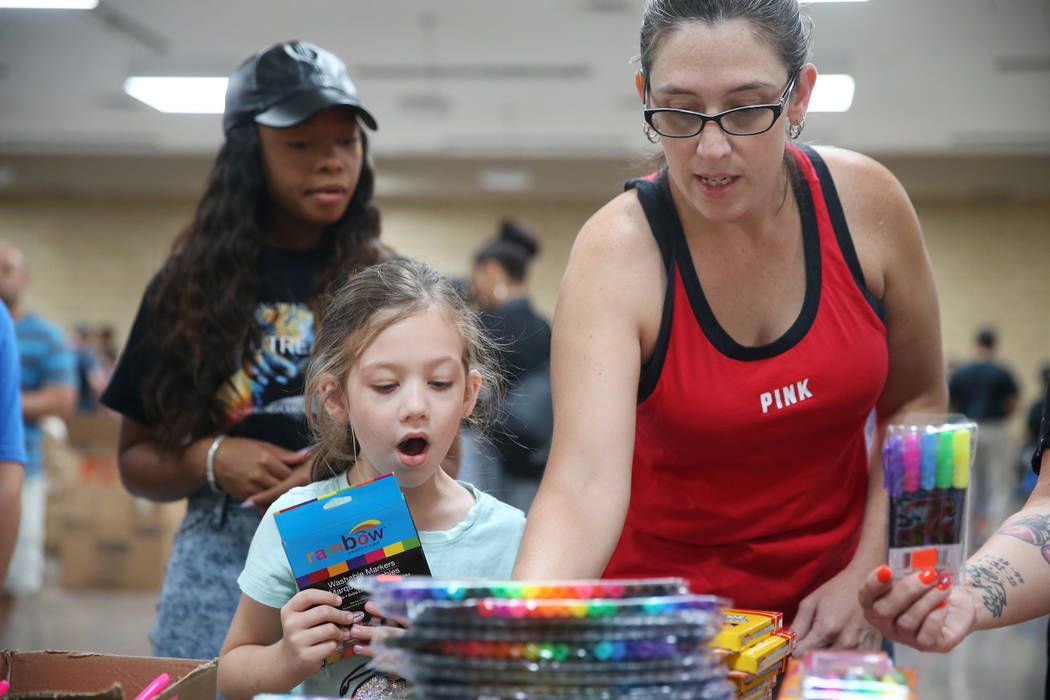 Danielle Dejarnette, right, with her daughter Aria, 6, select free school supplies during an ev ...