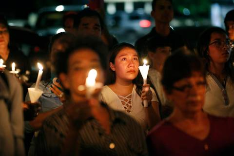 People attend a candlelight vigil for victims of a mass shooting at a shopping complex over the ...