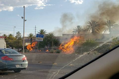 A fire burns near the southbound lanes of I-15 in Las Vegas on Thursday, Aug. 8, 2019. (Rochell ...