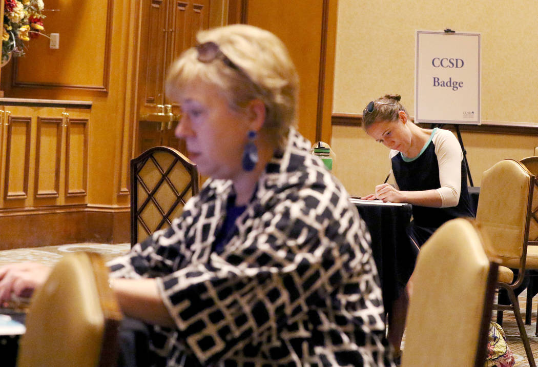 Ashley Robins, right, fills out forms during the Clark County School District new teacher hirin ...