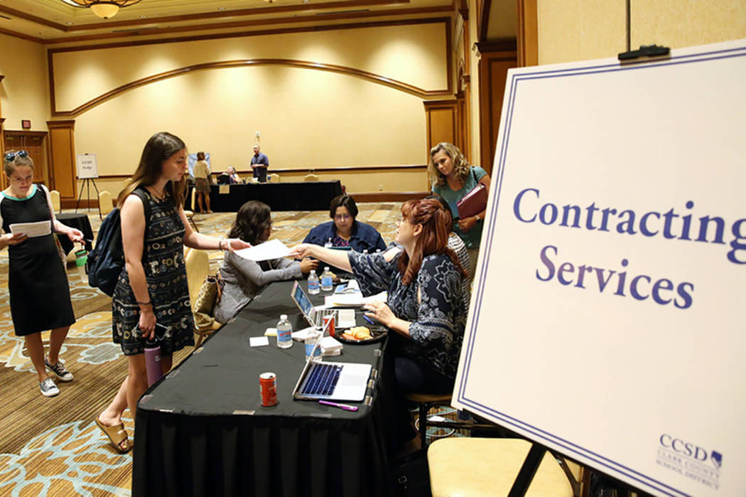 Ashley Robins, left, and Catherine McDonnell stand in line at Contracting Services desk during ...