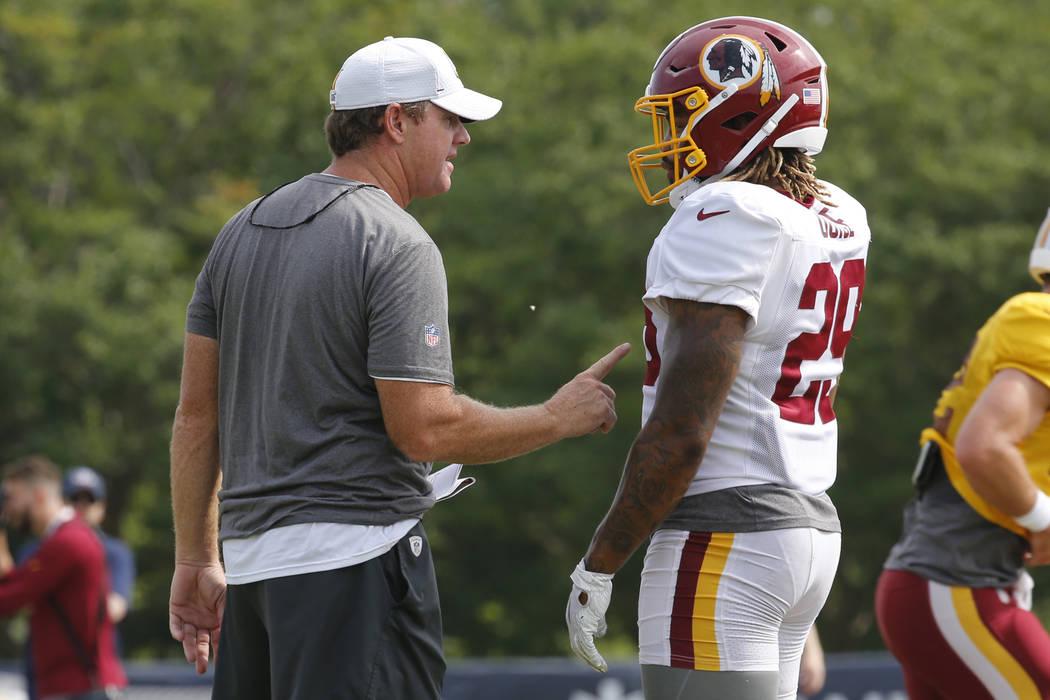 Washington Redskins head coach Jay Gruden, left, talks with running back Derrius Guice (29) dur ...