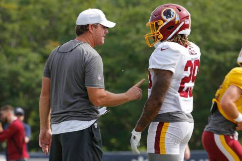 Washington Redskins head coach Jay Gruden, left, talks with running back Derrius Guice (29) dur ...