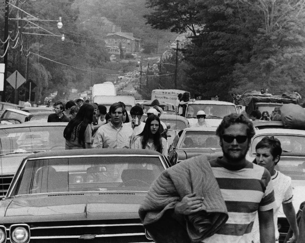 This Aug. 15, 1969 file photo shows people abandoning their trucks, cars and buses, backed up f ...